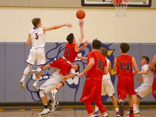 Fairfield Union Falcon Evan Conley goes over Bloom Carroll Bulldog Alan Meadows as Ethan Johson tries to block. The Falcons won over the Bulldogs 68-45 Saturday at Bloom Carroll Middle School.