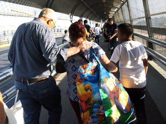 Ruben Garcia, director of the Annunciation House in El Paso leads a Guatemalan woman and her son across the Paso Del Norte Bridge. The mother and son planned to request asylum.