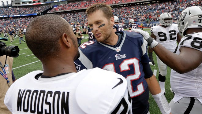 New England Patriots quarterback Tom Brady, right, speaks to Oakland Raiders safety Charles Woodson after a game Sept. 21, 2014, in Foxborough, Mass.