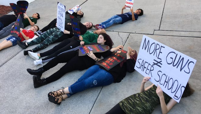 """In an April 2018 photo, a group of students and some teachers and parents staged a small """"die-in"""" protest before a town hall at Palm Bay High School auditorium. It was the first of three such meetings to get public input on a proposed marshal program to arm school staff."""