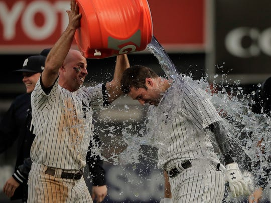 New York Yankees' Brett Gardner, left, douses Neil Walker after Walker hit a walkoff single to drive in Gary Sanchez for the winning run against the Oakland Athletics during the 11th inning of a baseball game, Saturday, May 12, 2018, in New York. (AP Photo/Julie Jacobson)