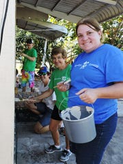 Melanie Dunnuck, foreground, Joanne Miller, Christian Nunnelee and Chris Nunnelee of TC3, also known as Treasure Coast Community Church of Stuart, paint a house in East Stuart on Feb. 24.
