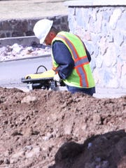A Town of Silver City employee works on College Avenue as part of a project to replace a main water line.
