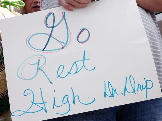 A sign is held during a memorial service for Dr. Drip,