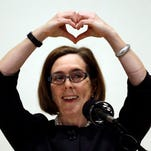 """Oregon Gov. Kate Brown forms a heart with her hands as she says """"I love Oregon"""" during her State of the State address in Portland, Ore., Friday, April 17, 2015. (AP Photo/Don Ryan)"""