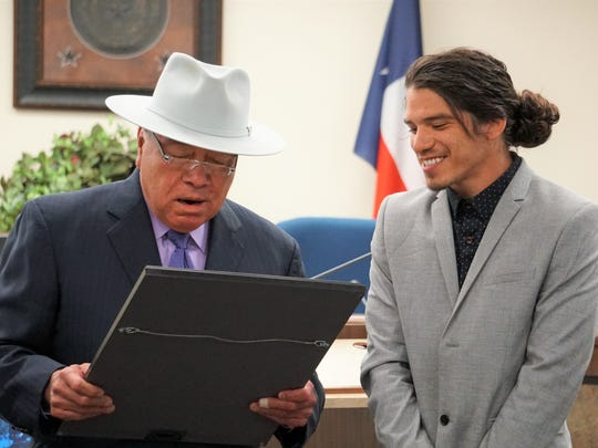 "Jeremy Flores listens as State Sen. Juan ""Chuy"" Hinojosa reads a proclamation honoring Flores' artistic contributions to the Corpus Christi community during a ceremony at the Nueces County Courthouse on Thursday, April 19, 2018."