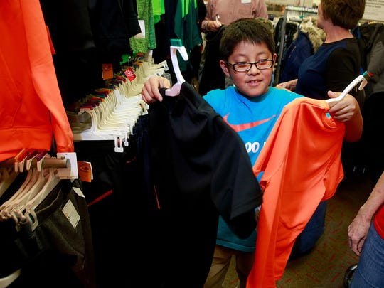 Anton Wilson, 8, tries to decide between two new shirts on Thursday during the Clothes for Kids event at Target.