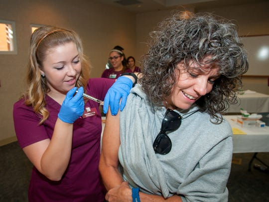 Mary Lujan gets her free flu shot from NMSU student nurse Kailene Ruttle at Memorial Medical Center's yearly flu clinic. Lujan has gotten a flu shot from the clinic every year since it opened.