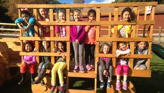 Daisy Troop 96855 went on a hayride and pumpkin picking at Abma's Farm. In the photo, the girls are playing on Abma's replica hayride wagon while they wait for the real hayride.