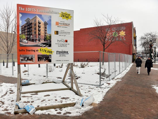 A sign advertises The LOFTS Condominiums as the parking