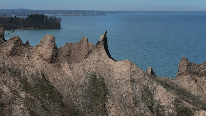 The view from the Bluff Trail at Chimney Bluffs State Park along Lake Ontario in Wolcott Friday, May 6, 2016.  In the distance, at center top above the largest eroded chimney, sits the Sodus Bay Beach Park light located at the end of the pier.
