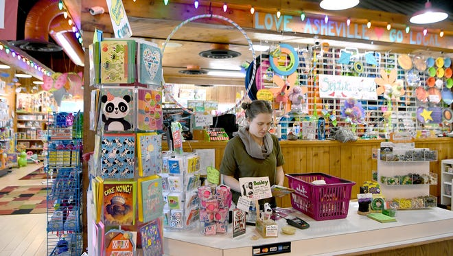 Madeline Owen helps a customer at Dancing Bear Toys in Asheville on Thursday, March 15, 2018. The store has a wide variety of toys and displays that allow children, and adults, to give many of them while visiting the store.