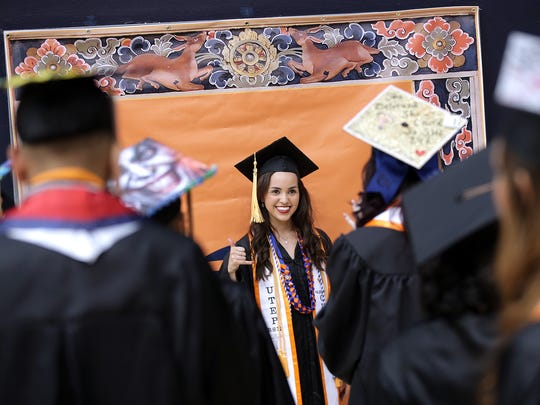 University of Texas at El Paso graduating seniors take photos against a backdrop at Memorial Gym before heading to the Don Haskins Center to receive their diplomas in May.