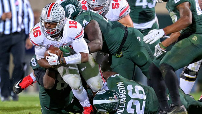 Nov 8, 2014; East Lansing, MI, USA; Ohio State Buckeyes quarterback J.T. Barrett (16) is tackled by Michigan State Spartans safety RJ Williamson (26) during the 2nd half of a game at Spartan Stadium.