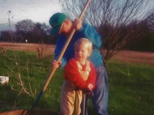 "Patty Pirko's son, Nick, at age 2, gardens with ""PawPaw"". The two often sold produce at local farmers markets. Nick is currently serving in the USMC."