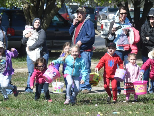 Children launch from the sidewalk as smiling relatives look on Saturday at Cooper Park during the 20th Annual Junior Auxiliary Easter Egg Hunt. Hundreds of parents and children enjoyed sunny skies as they hunted eggs.