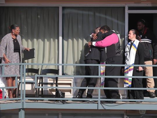 Rev. William Barber gets a hug as he prepares to address