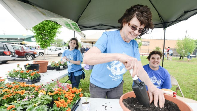 In this file photo, Barbara Michaud with Keep Jackson beautiful mixes soil at a planting station at the Earth Day Festival in Jackson.