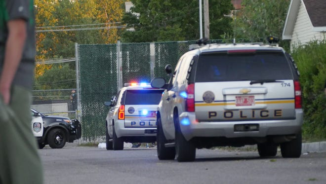 A body is visible lying on the pavement beyond two police cruisers on Hickok Street in Winooski following a police shooting Friday evening.