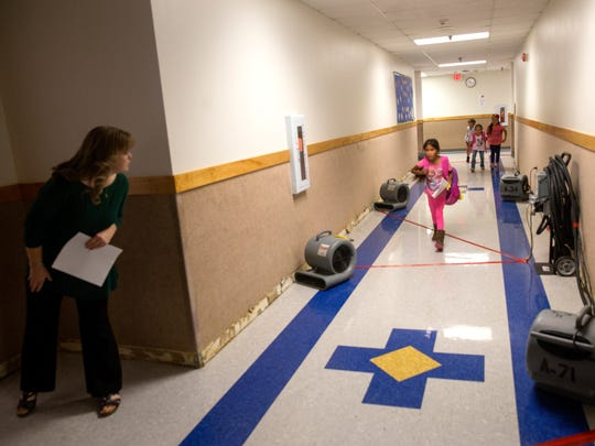 Teacher and students use a hallway Thursday near an area where water damage originated at Kirtland Elementary School.