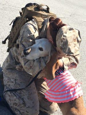 U.S. Marine and Madison graduate Baylie Scheurer hugs her basset hound, Sammy.