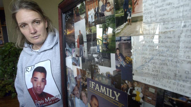 Christi Berry, the mother of Travis Monroe, a Worcester teen who was found dead in the roadway on Fales Street on October 1, 2006,    with a large collage of photos and mementos of her son, which was put together by neighbors and friends for her.
