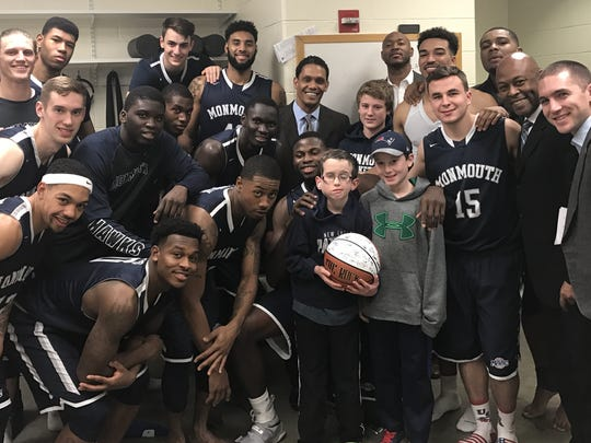 The Monmouth basketball team and coaches surround 10-year-old cancer patient Logan Schoenhardt (holding basketball) of West Simsbury, Conn., after their win at Quinnipiac on Dec. 1, 2016.