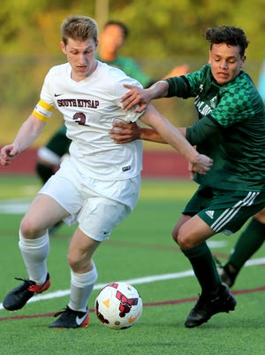 South Kitsap soccer player Quinn Dick fights off  Mount Vernon's Luis Rivera-Valles for the ball at South Kitsap on Wednesday. South lost the 4A state soccer playoff game 4-0.