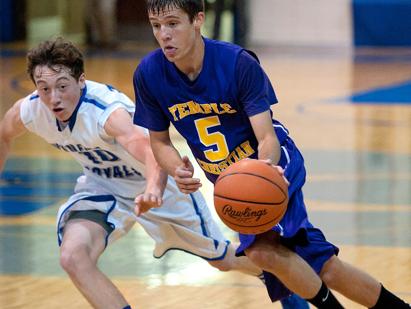 Temple Christian guard Darien Davis runs the ball downcourt with Wynford's Jack Reed in pursuit.