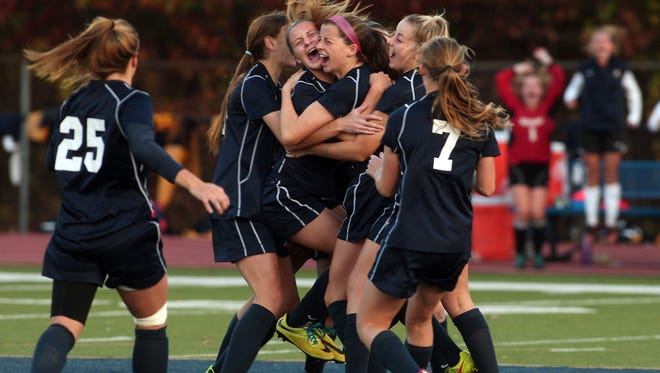 Roxbury teammates mob Paige Monaghan, c, after she scored 10 seconds into the game from the 50-yard line vs Randolph in the Morris County Tournament girls soccer final at Roxbury High School.  October 25, 2014, Roxbury, NJ. Photo by Bob Karp