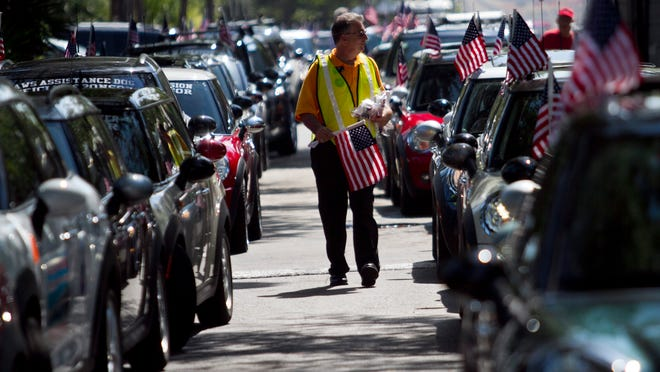 Kevin Powers of Mini of Fort Myers passes out flags to Mini drivers Saturday, before the group ride to Cape Coral. The event, which ended at The Tilted Kilt, was set up to raise funds for Operation Open Arms, an organization that provides vacations and weddings for troops.