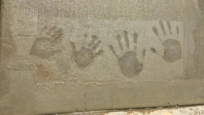 The hands of Meredith Cook and her son, Cutler, are captured in concrete at their new home, which will be dedicated on Friday, May 26, at 4 p.m.