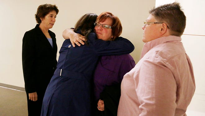 Attorney Carole Stanyar, left, looks on as her co-council Dana Nessel hugs April DeBoer and Jayne Rowse, right, at Afirmations in Ferndale today, before they address the media about the 6th Circuit Court of Appeals upholding the ban on gay marriage.