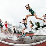 Racers leap over the pool of water during the 3000 meter steeple chase during the first day of the America East Track and Field Championship at the Frank H. Livak Track and Field Facility on Saturday in Burlington.