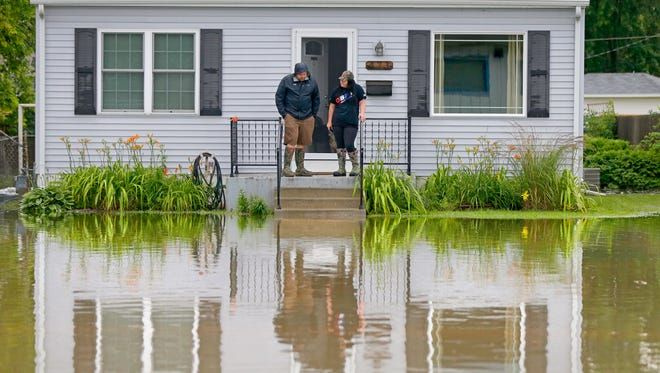 Jason O'Donnell and his wife Dee look at the floodwaters outside their home on Pine St. in Burlington in July. He said he had about 4 feet of water in his basement.
