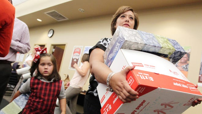 Wendy Fryer, a fourth-grade teacher at Ossun Elementary, and her daughter Lilah pick up donated school supplies at the 2014 Adopt-A-Teacher event.