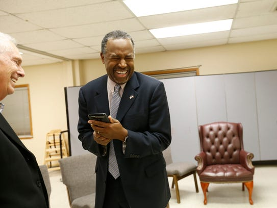 Republican presidential candidate Ben Carson laughs