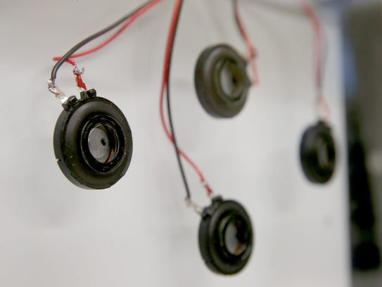 Small magnets attached to a prototype flat-panel speaker