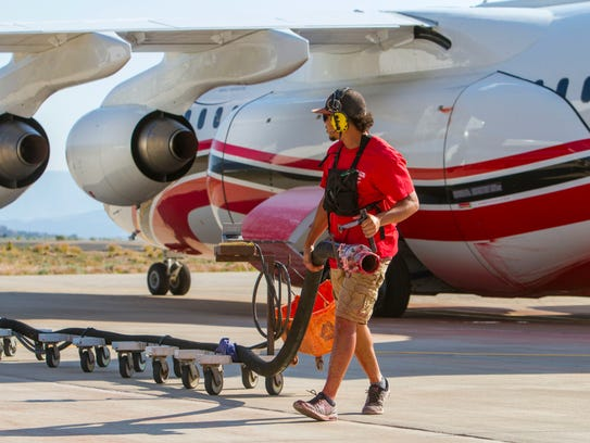 Crews help load planes with fire retardant at the Cedar