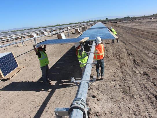 Construction workers build the 20-megawatt Apache Solar Project outside of Benson, Arizona.