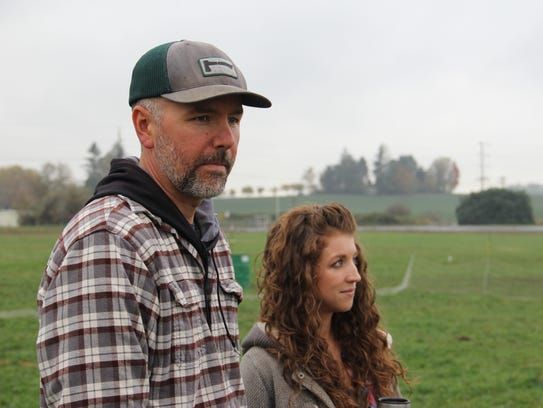 John and Rachelle Mathia stand in their pasture, where