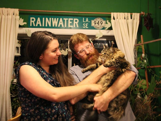 Elizabeth Schulte and Brian Russell hold their cat,