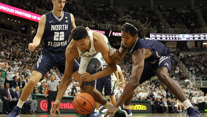 Nov 10, 2017; East Lansing, MI, USA; Michigan State Spartans forward Kenny Goins (25) and North Florida Ospreys forward Wajid Aminu (2) fight for a loose ball during the second half of a game at Jack Breslin Student Events Center.