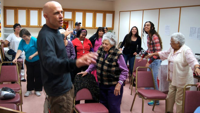"Fitness instructor Jeff Goin leads his group of senior citizens through the ""Reggae Hula"" on Wednesday. Goin has been teaching the free class for a year at the Silver City Senior Center."