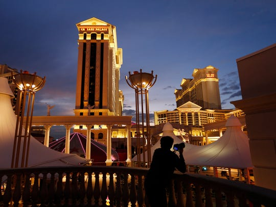 A man takes pictures of Caesars Palace hotel and casino,