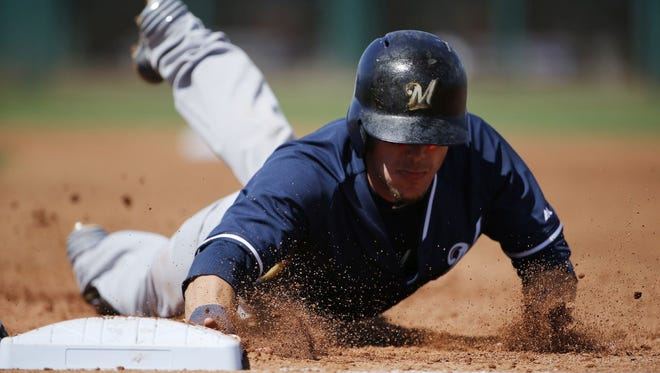 Milwaukee Brewers' Scooter Gennett dives safely back to first base during the third inning of a spring training baseball game against the Cleveland Indians Friday in Goodyear, Ariz.