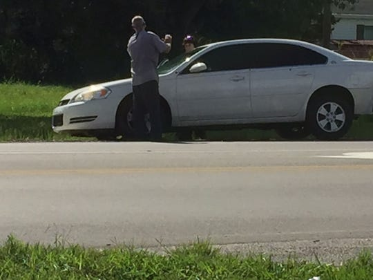 A white Chevy Impala with several bullet holes is prepared for towing on Monday. Three area men were arrested after a traffic stop and are considered persons of interest in the Club Blu shootings.