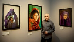 Photographer Steve McCurry poses in front of photographs