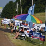 In this July 30 2015 photograph, Neshoba County fairgoers stroll past the campaign totem poles on Founders Square in Philadelphia, Miss., that are adorned with signs for virtually every type of candidate running in Tuesday's primaries. Mississippi's Democratic and Republican primaries will narrow the list of candidates for statewide offices such as governor, regional offices such as public service commissioner, legislative seats and county offices such as supervisor and sheriff. Polls will be open 7 a.m.-7 p.m.