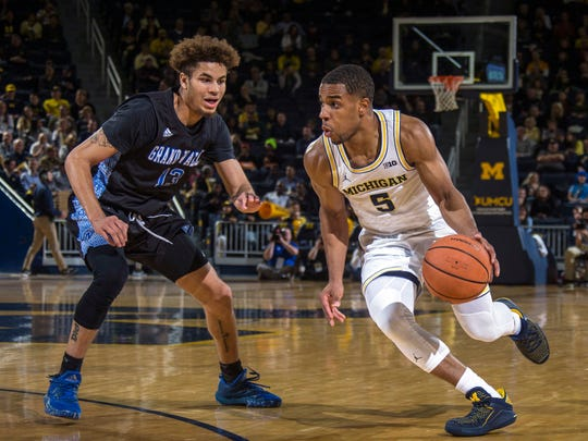 Grand Valley State's Hunter Hale defends Michigan's Jaaron Simmons in the first half of an exhibition Friday, Nov. 3, 2017 at Crisler Center in Ann Arbor.